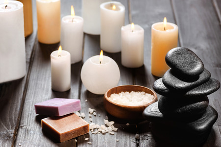 Close-up view of piled spa stones and candles with sea salt on wooden table top