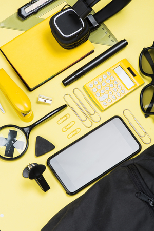 Close-up view of calculator, smartphone and school supplies on yellow