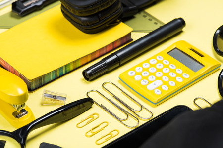 office stapler: Close-up view of headphones, calculator and various school supplies on yellow