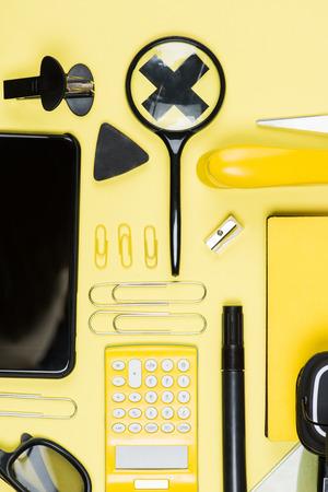 黄色の電卓、スマート フォンおよび学校供給のクローズ アップ ビュー