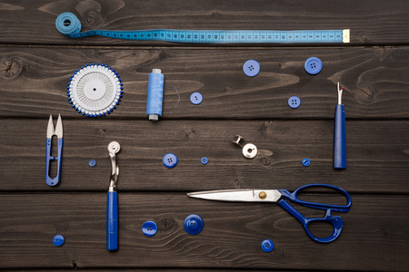 set of various sewing supplies on wooden surface