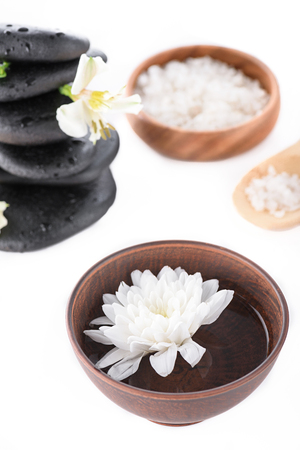 Zen stones, sea salt, wooden bowl with water and flower isolated on white, spa treatment concept