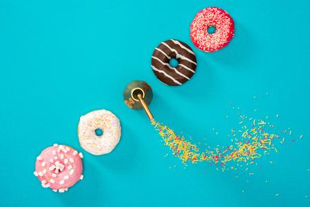 다채로운 유약 행에서 4 도넛의 오버 헤드보기. 파란색 배경에 고립 도너츠