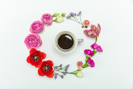 Top view of beautiful various blooming flowers around cup of coffee isolated on white Zdjęcie Seryjne