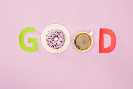 Top view of Good word made from donuts and cup of coffee isolated on pink