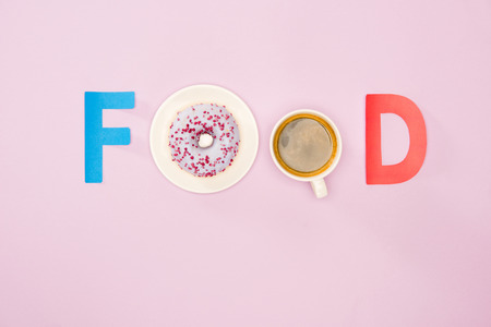 Top view of food word made from cup of coffee and donuts isolated on pink. junk food background