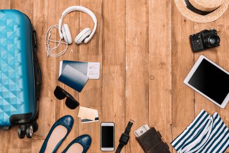 Planification d'un ensemble d'accessoires de voyage sur un plancher en bois. Appartement posé avec bagages, passeports, gadgets numériques et vêtements. Banque d'images - 80190385