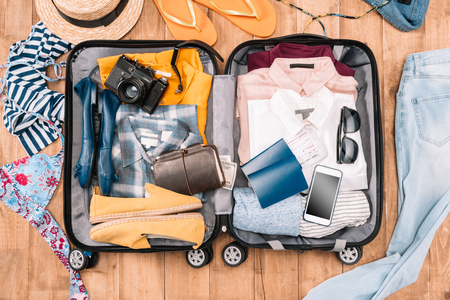 Overhead view of travelers accessories organized in open luggage on wooden floor