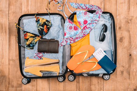 Top view of open luggage full of womans clothes and other essential vacation items. Ready to summer vacation Stock Photo