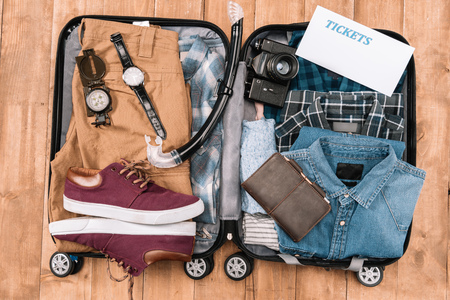 Top view of open luggage full of men clothes, gadgets, and other essential vacation items. Ready to summer vacation Stock Photo