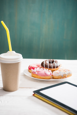 Unhealthy breakfast with coffee to go, plate of frosted donuts and digital tablet with white screen on wooden table. donuts and coffee background Zdjęcie Seryjne