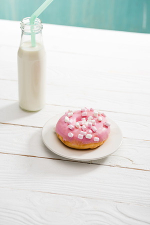 Donut with pink icing and fresh milkshake on wooden surface Stock Photo