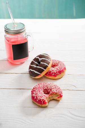 초콜릿과 베리 설탕 프로 스 팅을 얹은 도너츠와 함께 베리 주스 스톡 콘텐츠