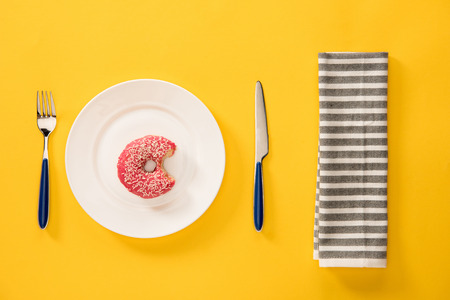 Overhead view of bitten donut with pink glaze in plate and napkin  isolated on yellow. background in minimalist style