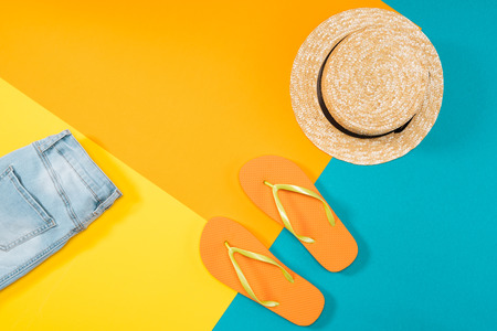 Summer vacation background with orange flip flops, denim trousers and hat on colored copy space Stock Photo