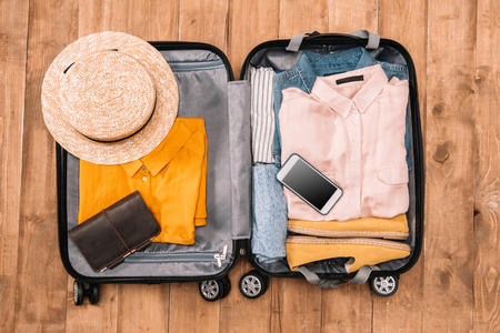 Top view of open luggage full of clothes, document and smartphone on wooden floor, Summer travel concept