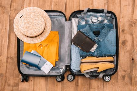 Prêt pour le concept de voyage. Vue de dessus de l'essentiel pour les touristes avec des vêtements, des accessoires et des gadgets, portefeuille, passeport, smartphone en sac. Banque d'images - 80233395