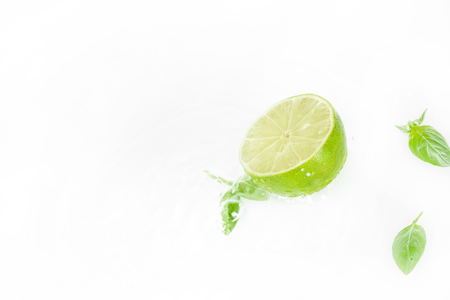 half of lime with green leaves and water drops isolated on white, fresh fruits background