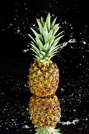 Close-upmening van verse rijpe die ananas met waterdalingen op zwarte worden geïsoleerd