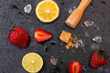 houten pers met citroen en aardbeien plakjes op stenen bord, barman cocktail