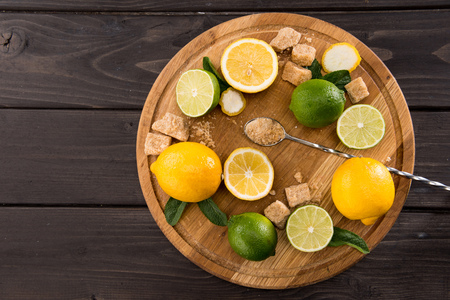 top view of lemons and limes with brown sugar on wooden kitchen board, barman cocktail Stock Photo