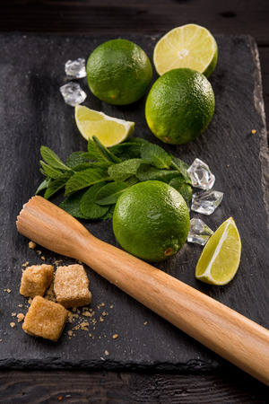 lime slices with brown sugar and wooden squeezer on stone board, barman cocktail Stock Photo