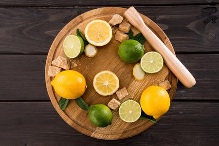 bovenaanzicht van citroenen en limoenen (lemmetjes) met bruine suiker op houten keuken bord, barman cocktail