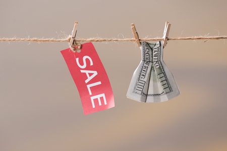 sale sign and one hundred us dollar banknote on clothesline, offer sale concept Reklamní fotografie
