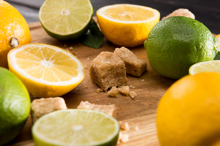 close up of lemons and limes with brown sugar on wooden kitchen board, barman cocktail