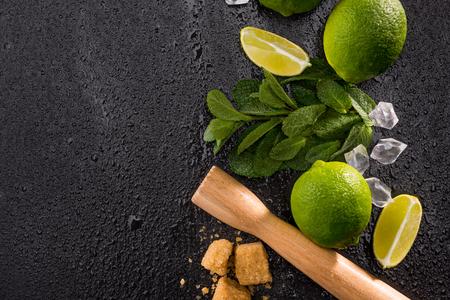 limoen plakjes met bruine suiker en houten knijper op stenen bord, barman cocktail achtergrond