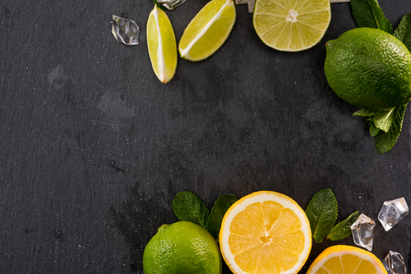 lime and orange slices with mint leaves and ice on stone board, barman cocktail background