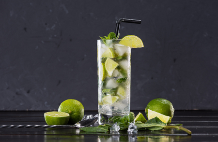 Close-up view of mojito cocktail in glass, sliced limes and mint on black, cocktail drinks concept Stock fotó - 80198487