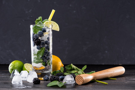blueberry and blackberry lemonade in glass with straw, cocktail bar background concept Stock Photo