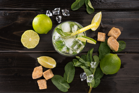 Top view of mojito cocktail in glass and fresh ingredients on dark wooden table top, cocktail drinks concept