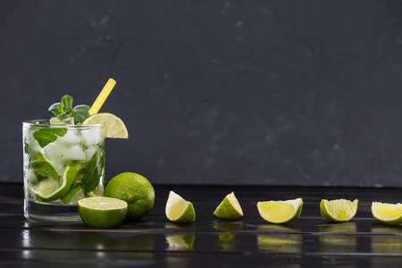 Close-up view of mojito cocktail with straw in glass and lime slices on black, cocktail drinks concept