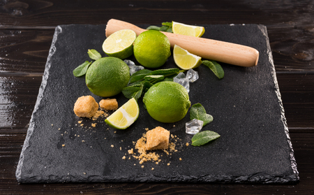 lime slices with brown sugar and wooden squeezer on stone board, barman cocktail 版權商用圖片