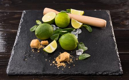 Limoenplakken Met Bruine Suiker En Houten Knijper Op Stenenplank, Barman Cocktail Stockfoto