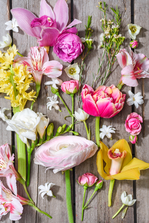 Top view of beautiful various blooming flowers on wooden table