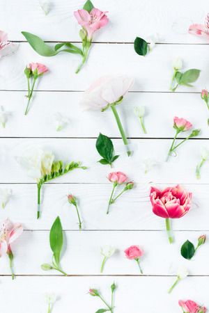 Top view of beautiful blooming flowers with green leaves on wooden table Stock Photo