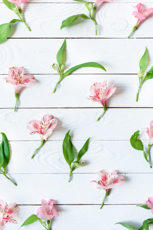 Top view of beautiful pink orchids with green leaves on wooden table