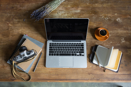 laptop, diaries, vintage photo camera and cup of coffee on wooden tabletop Stock Photo