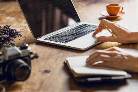 person using laptop and diary at workspace with vintage camera Stockfoto