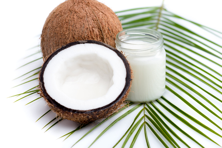 ripe coconuts and organic coconut oil in glass jar on coconut leaf