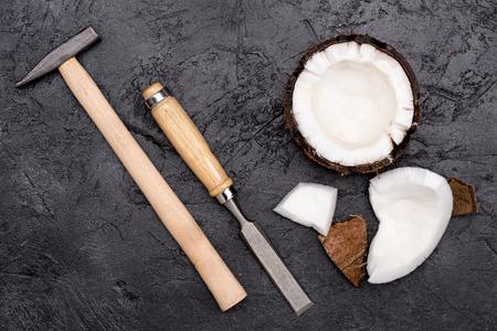 Coco roto con martillo y cincel en negro Foto de archivo - 80277451