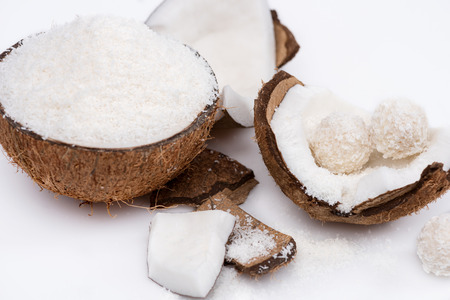 ripe coconut with shavings and sweet tasty candies isolated on white Фото со стока