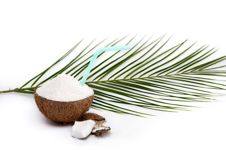 half of tasty coconut with shavings and straw and green palm leaf isolated on white Stock Photo
