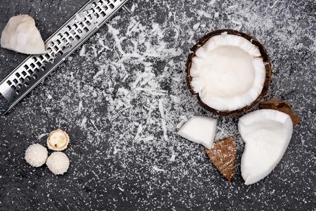 fresh broken coconut with shavings on black Фото со стока