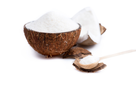 ripe organic coconut with sweet shavings with wooden spoon