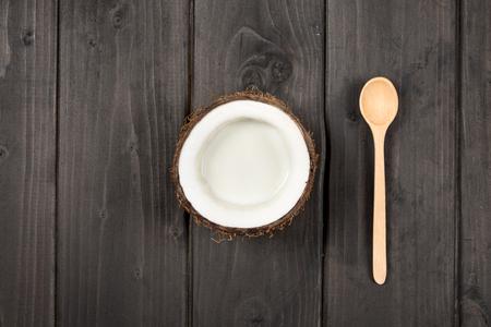 top view of ripe coconut half with milk and wooden spoon Archivio Fotografico