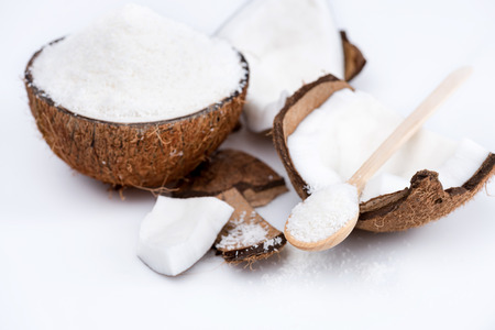 ripe organic coconut with sweet shavings with wooden spoon isolated on white